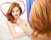 红发女孩附近与心脏在它在浴室的镜子. — 图库照片