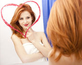 Redhead girl near mirror with heart at it in bathroom. — Foto de Stock