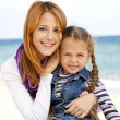 Two sisters 5 and 22 years old at the beach in sunny autumn day. — Stock Photo