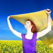 Young woman with open arms keep yellow silk on wind at rapeseed — Stock fotografie