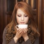 Style redhead girl drinking coffee near wood doors. — Stock Photo