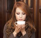 Rödhårig tjej dricker kaffe nära trä dörrar. — Stockfoto