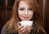 Style redhead girl drinking coffee near wood doors. — Stock Photo