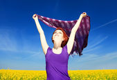 Young woman with open arms keep yellow silk on wind at rapeseed — Stock Photo