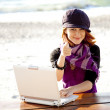 Portrait of red-haired girl with laptop at beach. — Stock Photo