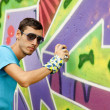 Graffiti painter drawing a picture on the wall - Stock Photo