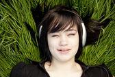 Brunetka dziewczynka słuchania muzyki na zielonej trawie. — Zdjęcie stockowe