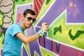 Graffiti painter drawing a picture on the wall — Stock Photo