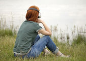 Young fashion girl with headphones at grass near lake in spring — Stock Photo