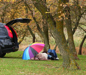 Couple lying near car at outdoor. — Stock Photo