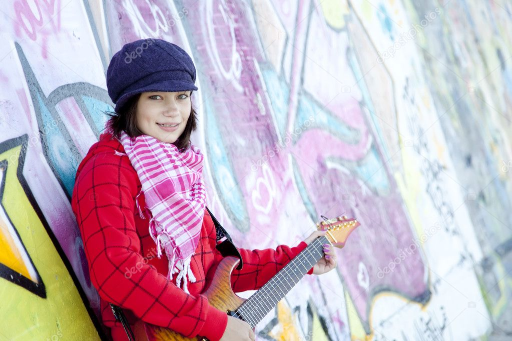 Closeup portrait of a happy young girl with guitar and graffiti on background — Stock Photo #8402138