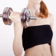 Attractive teenage girl working-out with dumbbells — Stock Photo #8568039