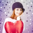 Royalty-Free Stock Photo: Beautiful red-haired girl in cap with toy heart.
