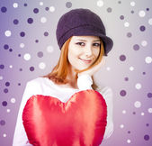 Beautiful red-haired girl in cap with toy heart. — Stock Photo