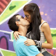 Two kissing near graffiti. - Stock Photo