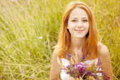 Redhead girl at outdoor with flowers. — Stock Photo