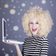 Portrait of funny girl in blonde wig with laptop. — Stock Photo