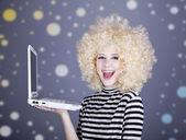 портрет смешная девочка в блондинка парик с ноутбуком. — Стоковое фото
