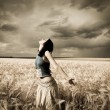 Girl at wheat field. Photo in dark colors with little noise. — Stock Photo