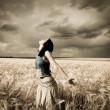 Stock Photo: Girl at wheat field. Photo in dark colors with little noise.