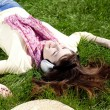 Brunette girl with headphone lies in the park. — Stock Photo #9081456