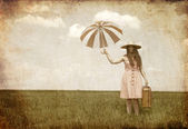 Brunette enchantress with umbrella and suitcase at spring field. — Stock Photo