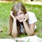 Blonde girl doing homework at the park. — Stock Photo #9209132