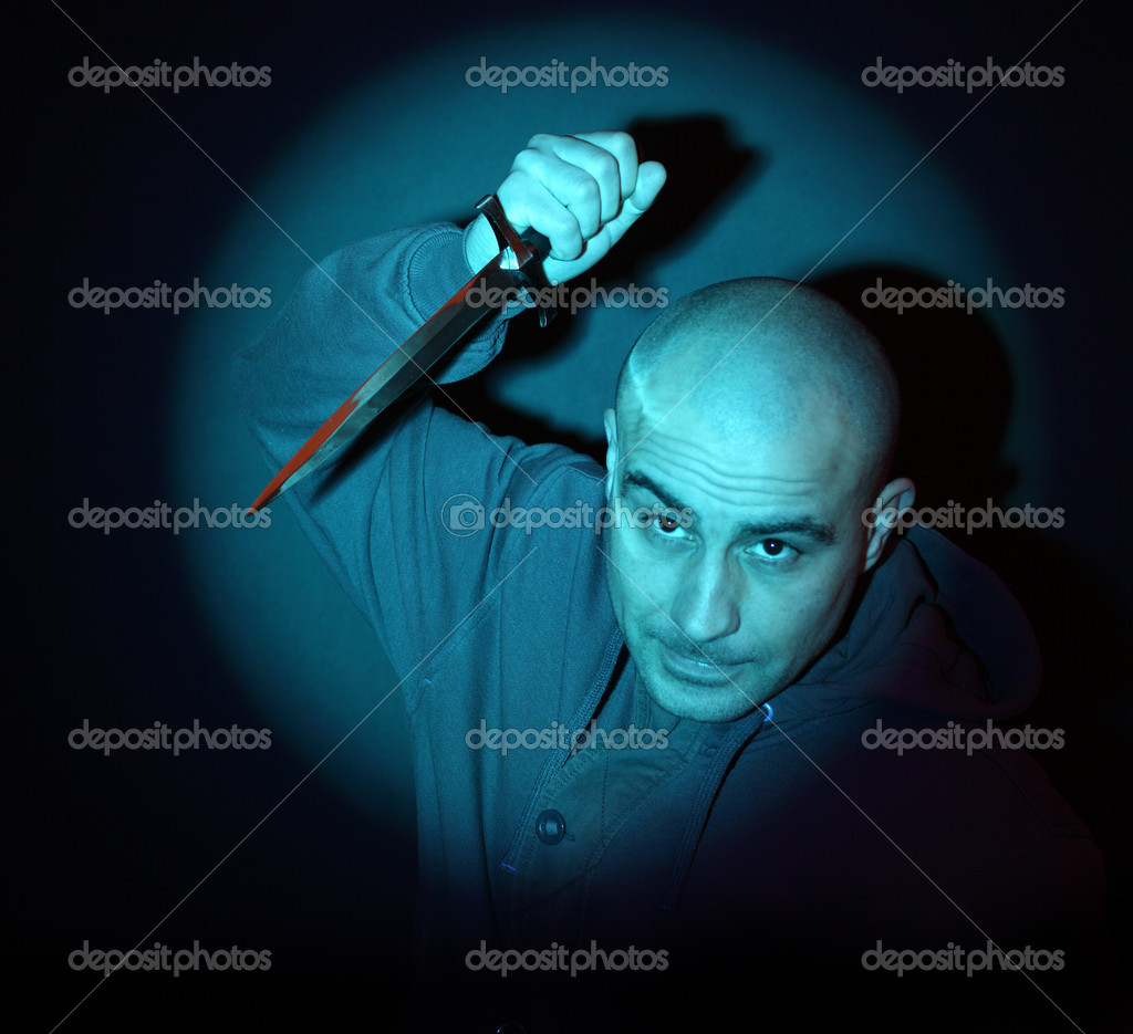Scary man with knife illuminated by a blue spotlight — Stock Photo #9063408
