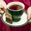 Tea bag with a cup of tea — Stock Photo