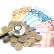 Постер, плакат: Concept of expensive healthcare with coins notes and stethoscope