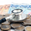 Concept of expensive healthcare with coins,notes and stethoscope - Stock Photo