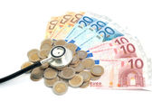 Concept of expensive healthcare with coins,notes and stethoscope — Stock Photo