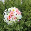 Pink and white wedding bouquet in green grass — Stock Photo