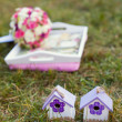 Two wooden house on the grass, background of pink and white wedd — Stock Photo
