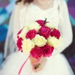 Pink and white wedding bouquet of roses in the hands of the brid — Stock Photo