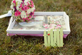 Pink and white wedding bouquet on the grass — Stock Photo