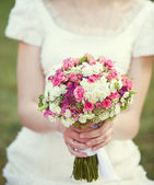 Pink and white wedding bouquet in the hands of the bride — Stock Photo