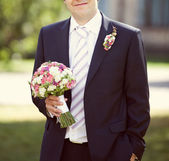 Pink and white wedding bouquet in the hands of the groom — Stock Photo