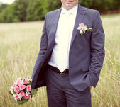 Pink and white wedding bouquet of roses in the hands of the groo — Stock Photo