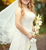 Bridal bouquet of orchids in the hands of the bride — Stock Photo