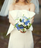 Bridal bouquet of white and blue flowers in the hands of the bri — Stock Photo