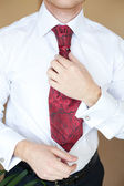 The groom in a white shirt and red tie — Stock Photo