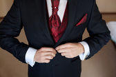 Groom in a wedding jacket and red tie — Stock Photo