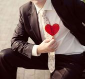 Groom in a wedding jacket with a red heart on his hand — Stock Photo