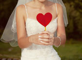 Bride with a red heart in hands — Stock Photo