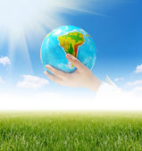 Globe in hands under blue sky — Stock Photo