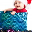Adorable christmas child in a red hat as a gift — Stock Photo