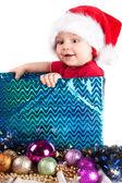 Adorabile bambino di natale in un cappello rosso come un dono — Foto Stock