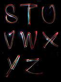 Alphabet light neon writing long exposure — Stock Photo