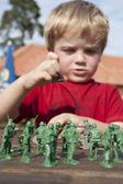 Young child playing soldiers and armies outside in the summer — Stock Photo
